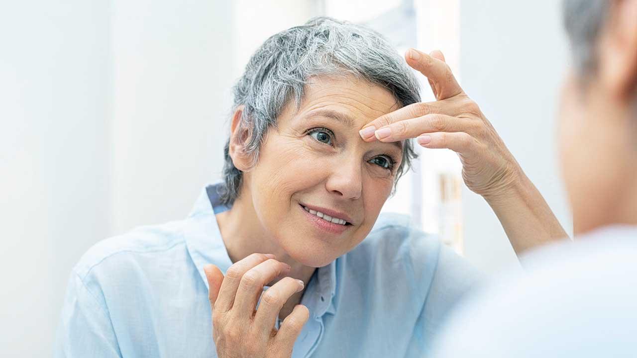 Frau begutachtet ihrer Haut im Badezimmer-Spiegel