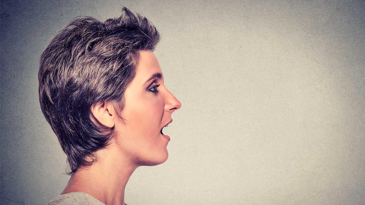 Seitlicher Blick auf eine Frau, die ihren Mund geöffnet hat