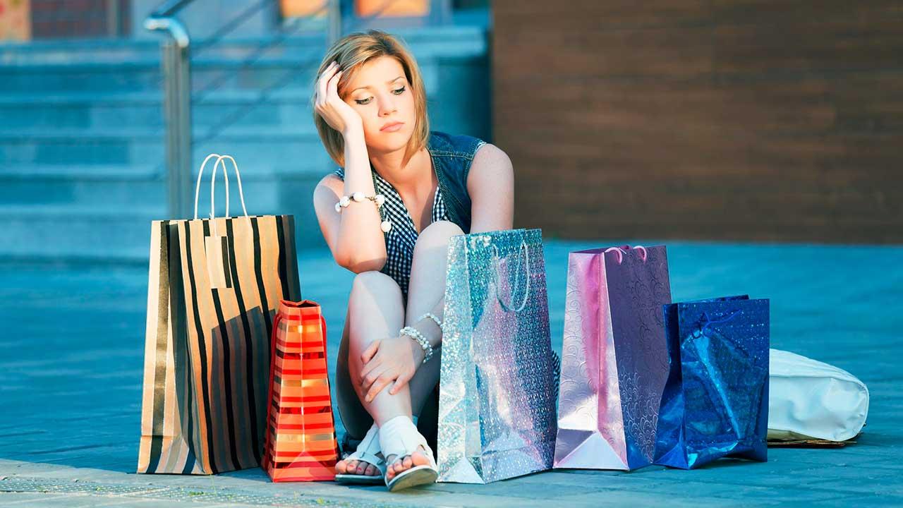 Frau sitzt enttäuscht und müde neben Einkaufstaschen