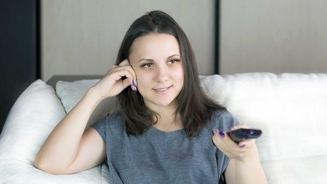 Junge Frau sitzt auf Sofa und hält Fernbedienung in der Hand