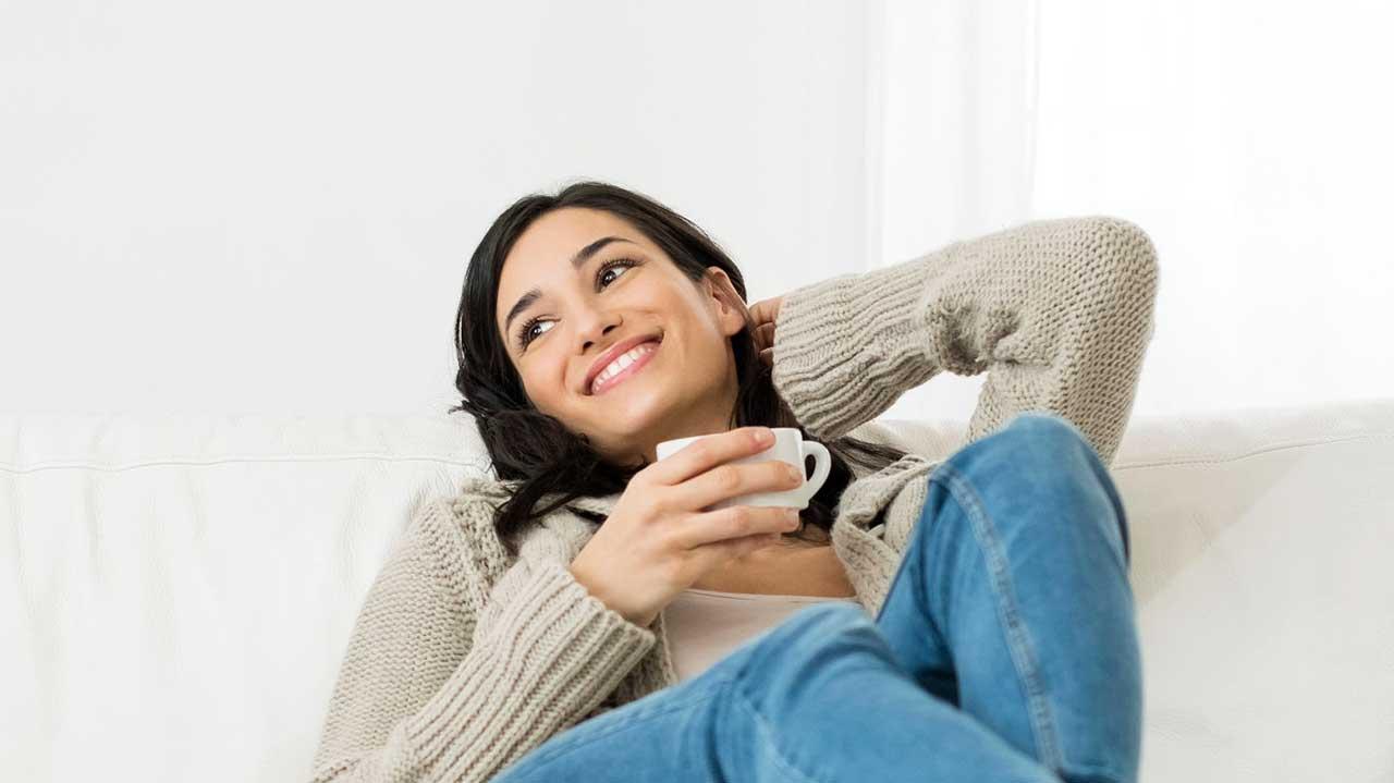 Eine junge Frau sitzt entspannt auf dem Sofa und lächelt