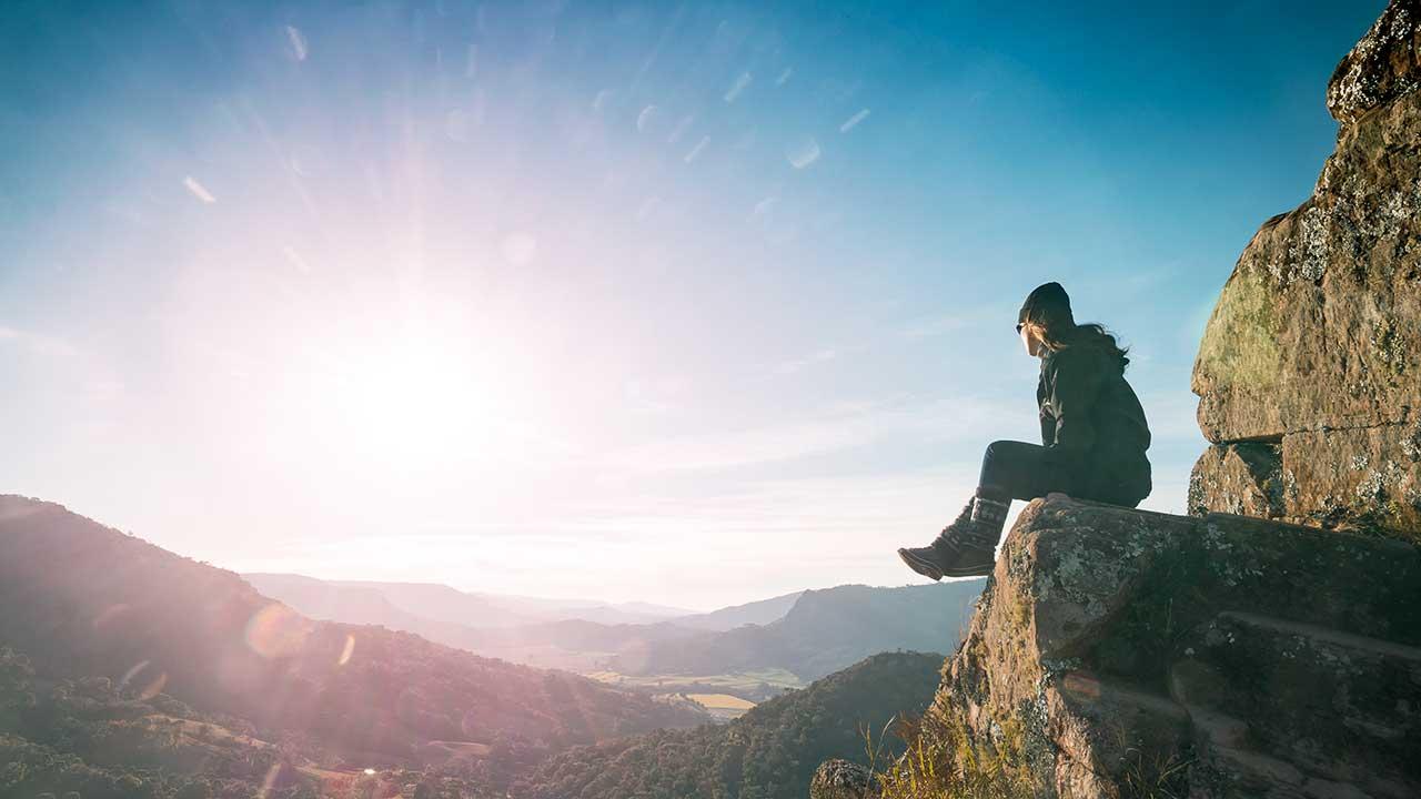 Frau sitzt auf einem Felsen und blickt ins Sonnenlicht