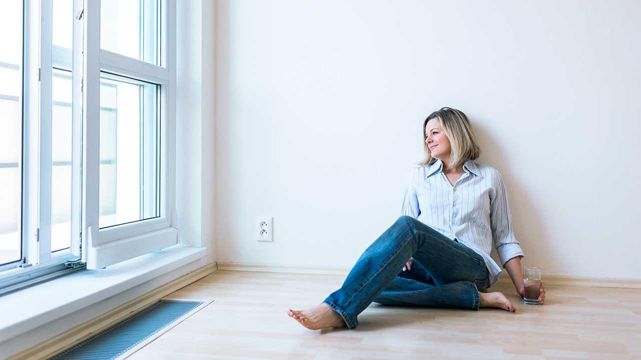 Zufriedene und gelassene Frau sitzt am Boden ihrer Wohnung