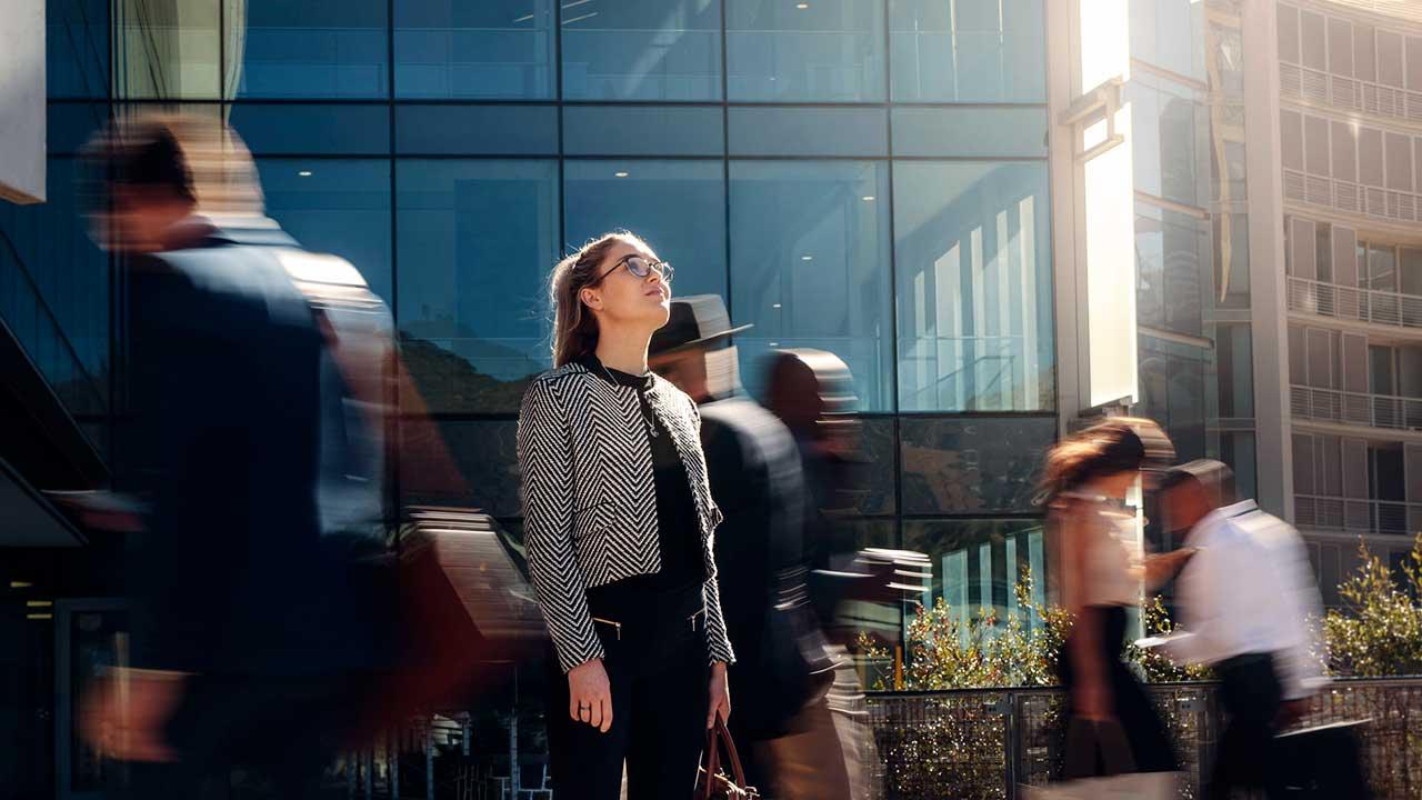 Frau blickt zuversichtlich nach oben, Passanten laufen an ihr vorbei