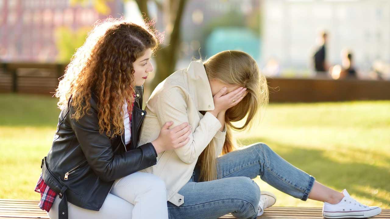 Junge Frau tröstet ihre Freundin