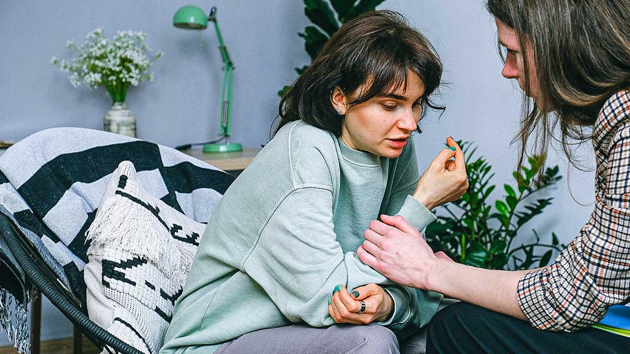 Eine Frau wendet sich fürsorglich einer anderen zu