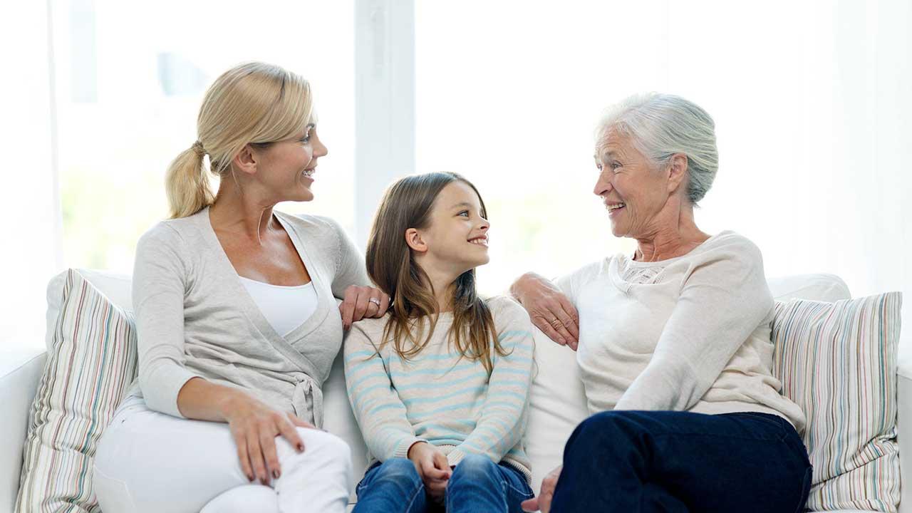 Drei Generationen von Frauen auf einem Sofa