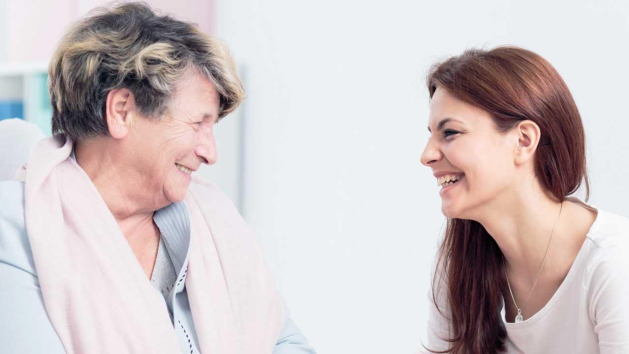 Zwei Frauen sitzen auf Sofas und haben eine herzliche Beziehung zueinander