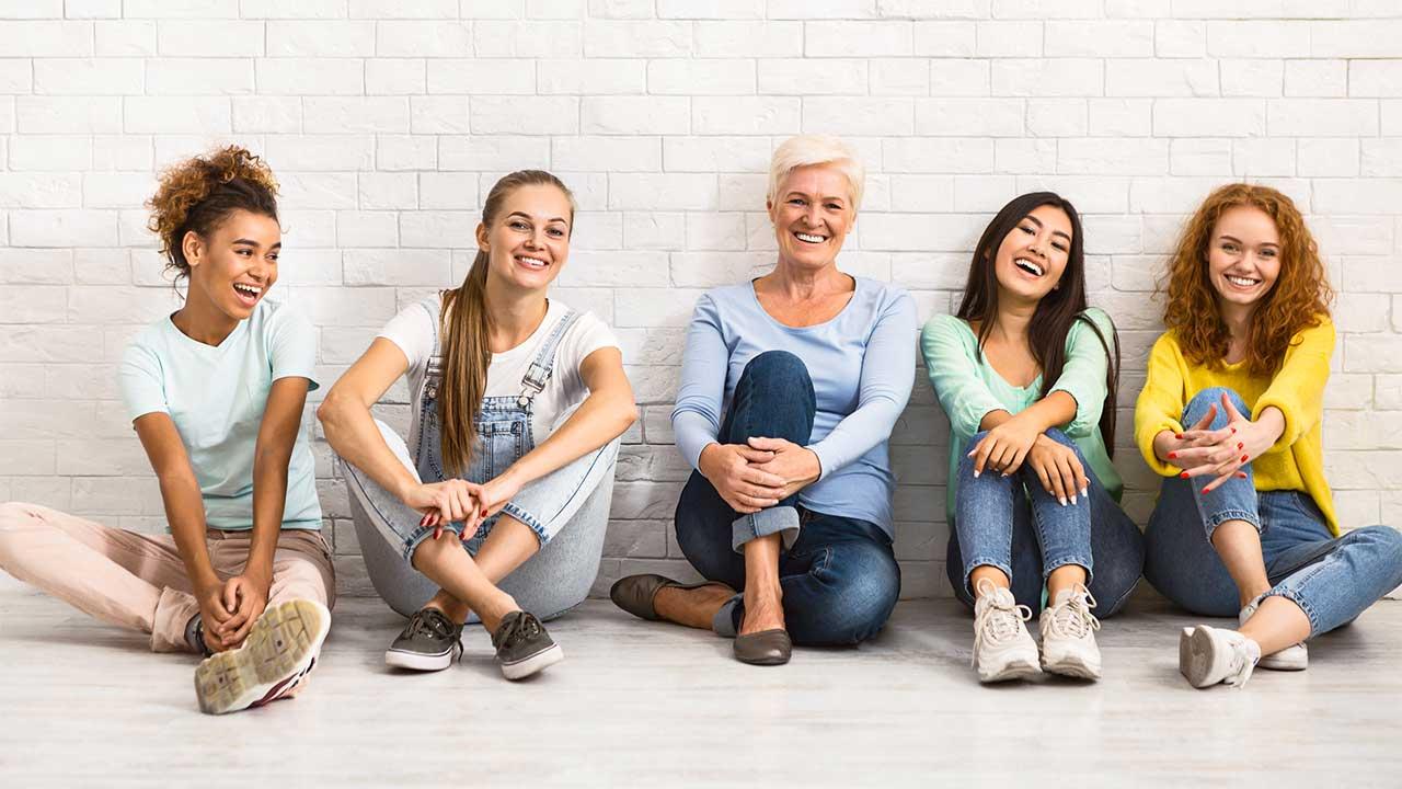 Gruppe von fünf Frauen sitzt vor einer Wand