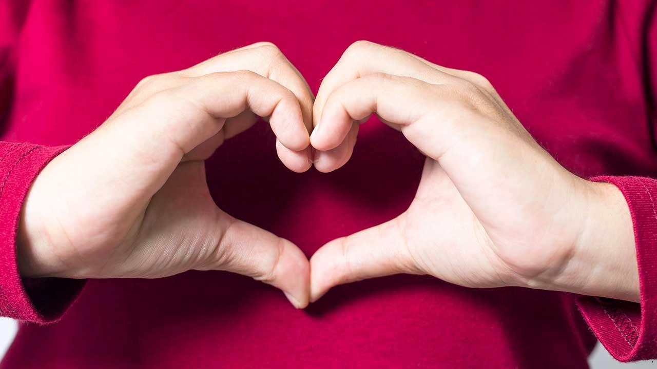 Frauenhände formen ein Herz