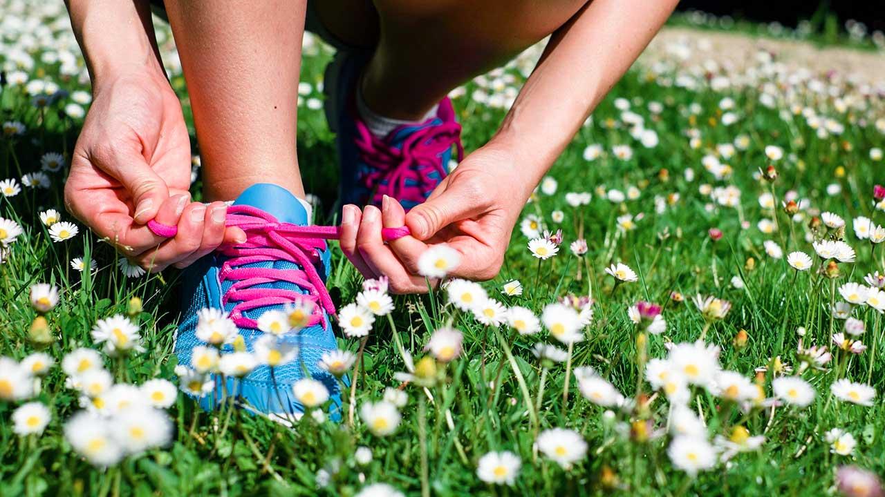 Frauenhände binden Schuhe