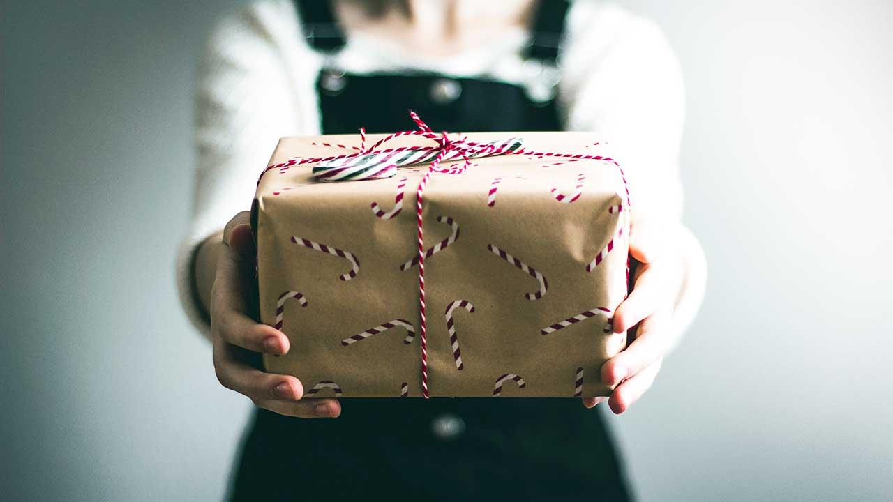 Frauenhände überreichen ein Geschenk