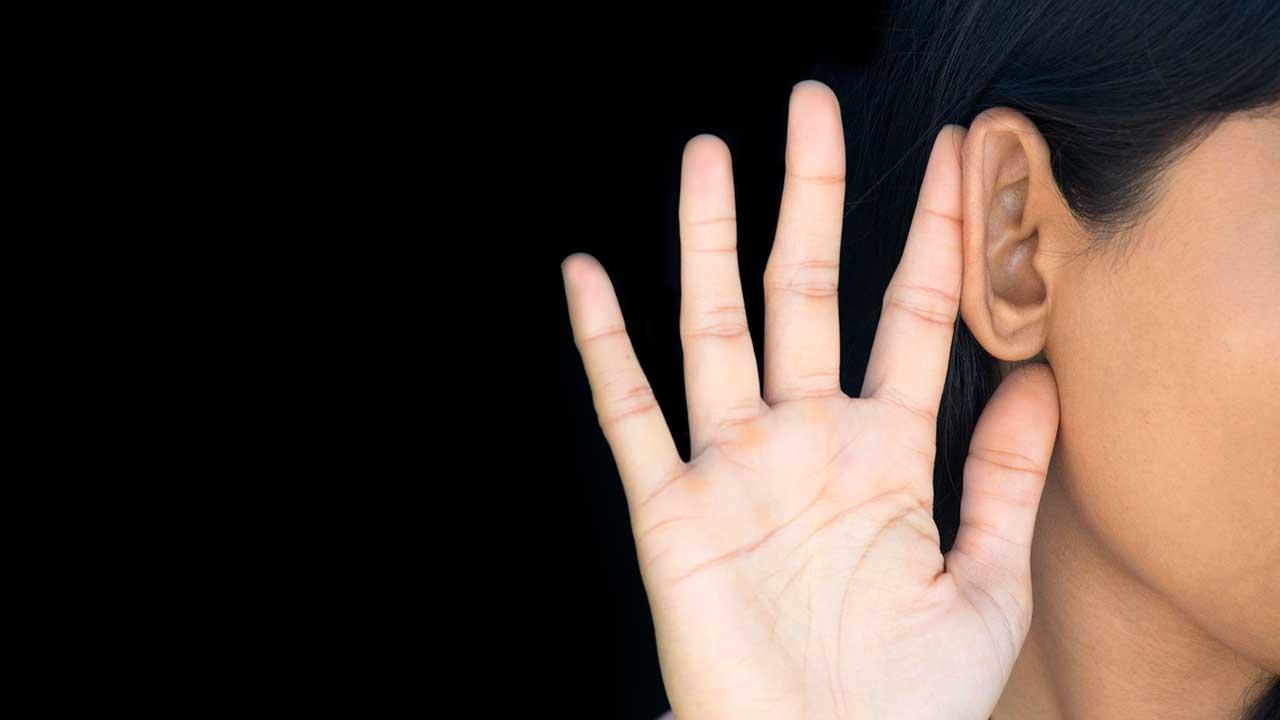 Frau hält Hand an Ohr, um genau hinhören zu können