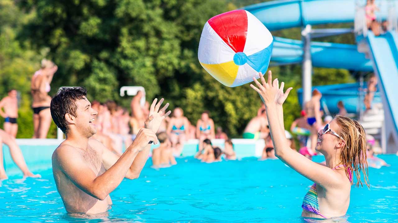 Paar spielt in einem Freibad mit einem aufblasbaren Ball