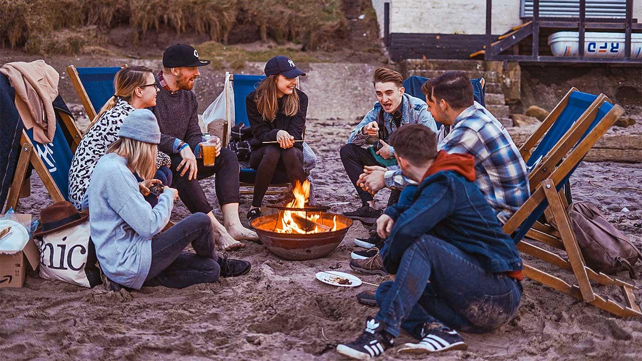 junge Menschen sitzen um ein Feuer herum und haben Gemeinschaft