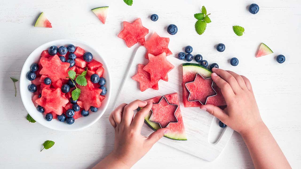Kinderhände bereiten kreatives Dessert mit Früchten zu