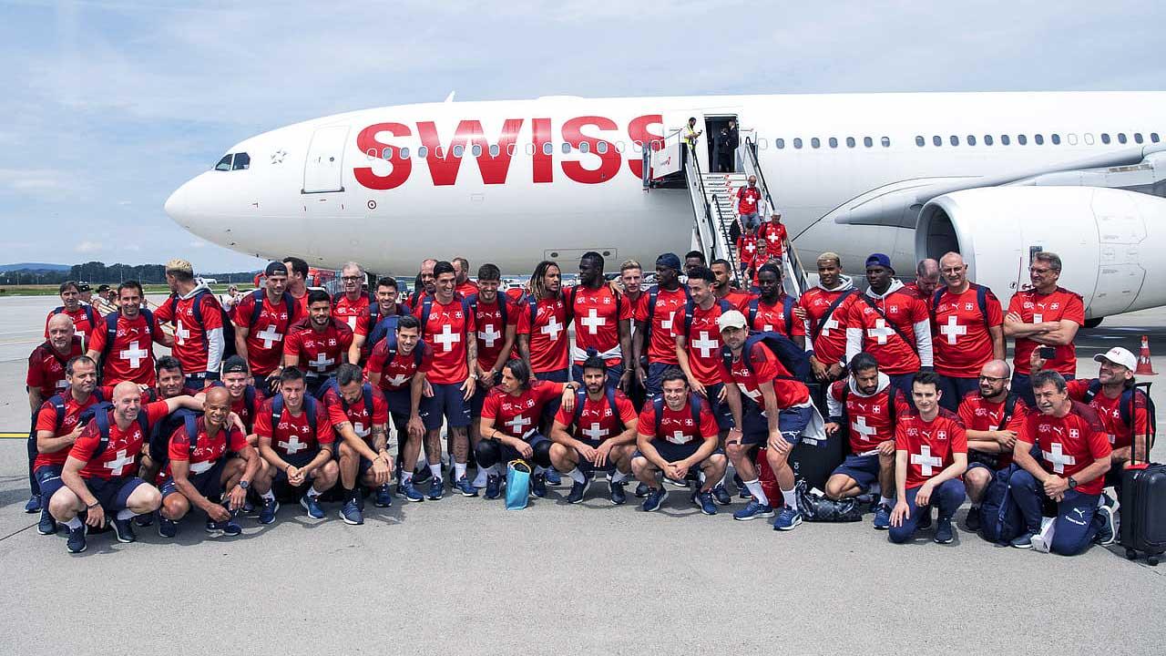 Das Team der Schweizer Fussball-Nati vor einem Flugzeug der Swiss am Flughafen Zürich-Kloten