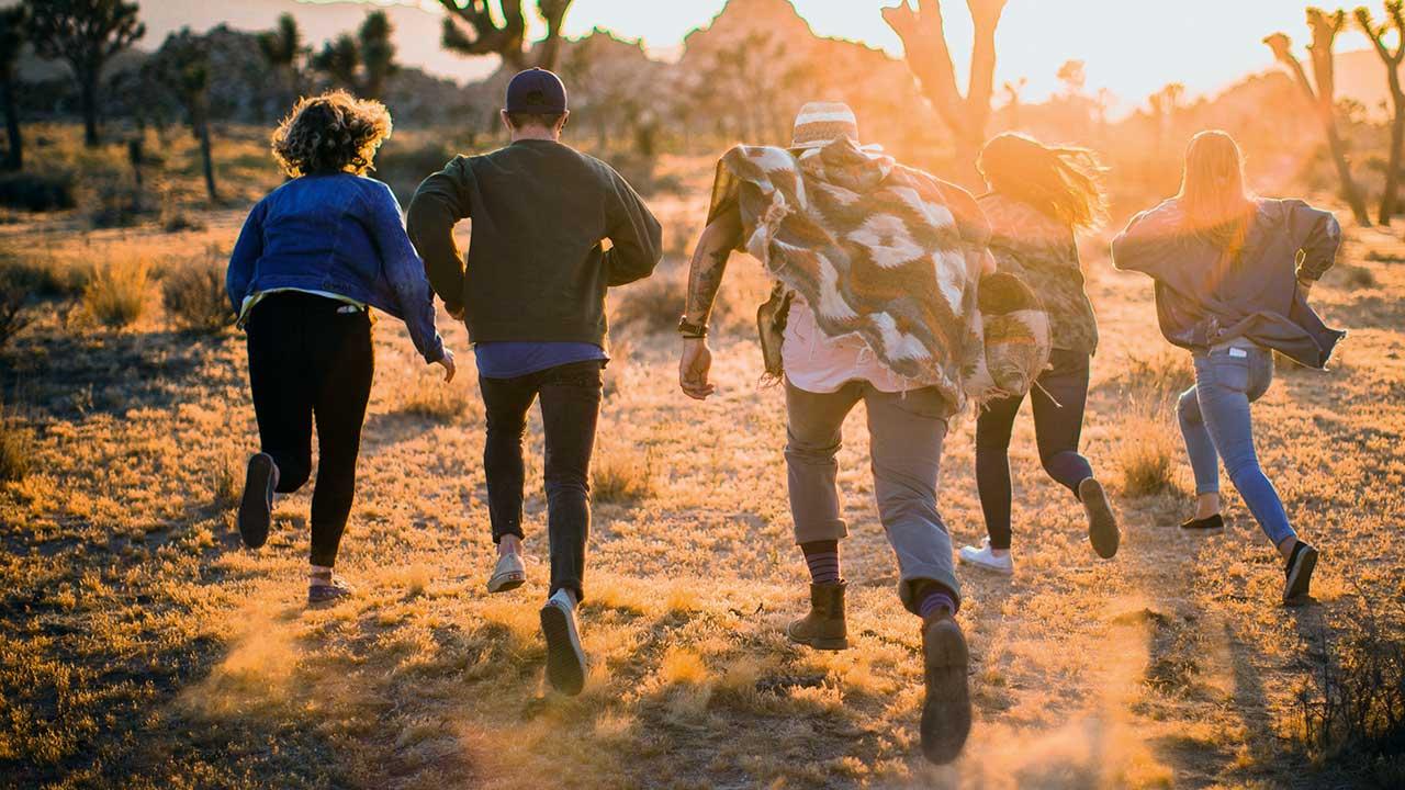 Gruppe rennt dem Sonnenlicht entgegen