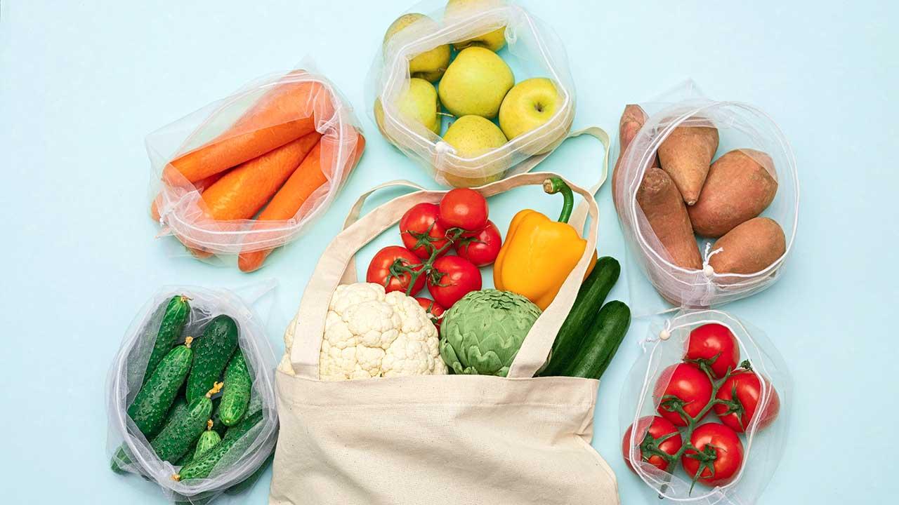 Gemüse und Früchte in Tüten und einer Baumwolltasche