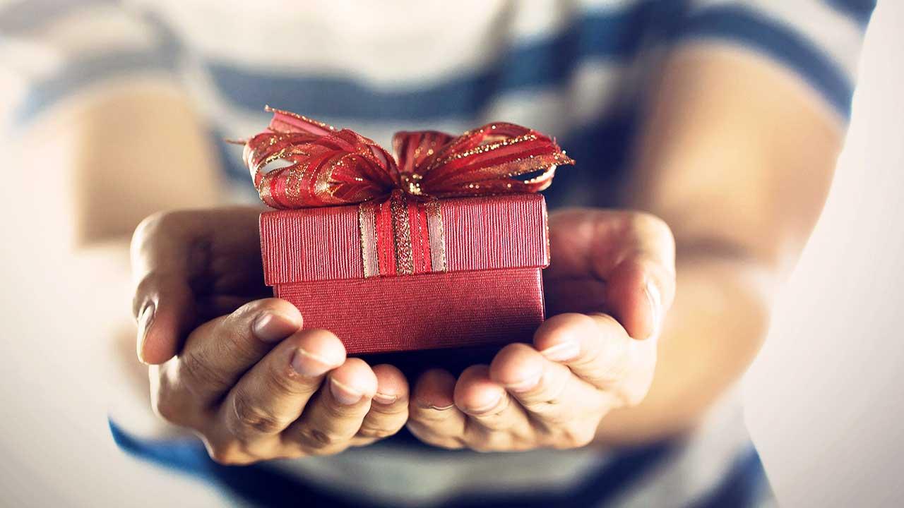 Hände bieten ein Geschenk dar