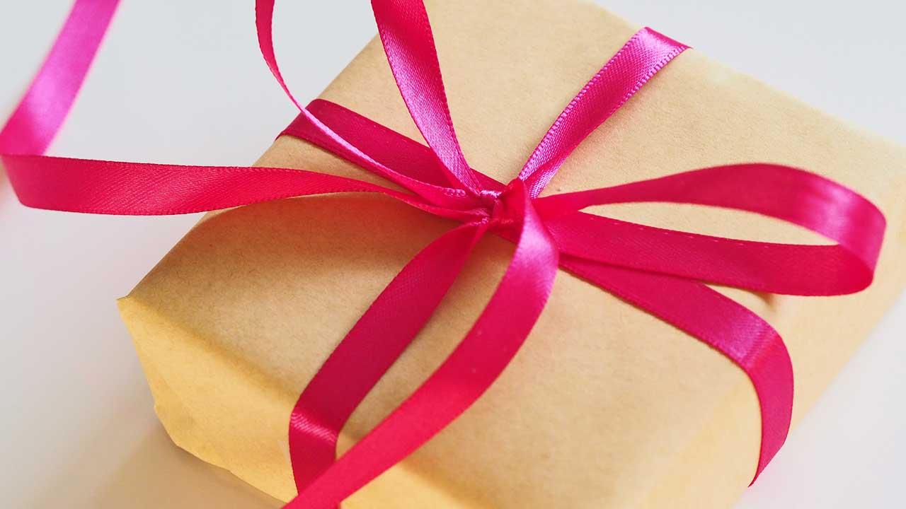 Geschenk in beigem Papier und mit roter Schleife