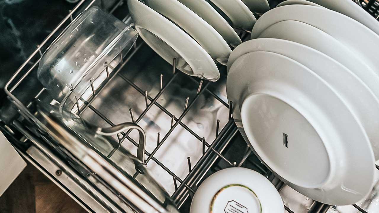 Offene Geschirrspülmaschine mit Tellern