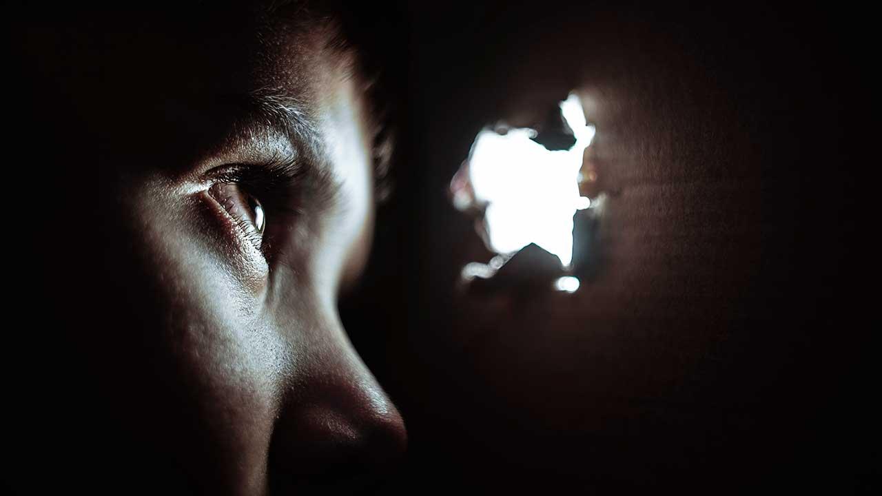 Gesicht in der Dunkelheit blickt durch ein Loch mit Licht