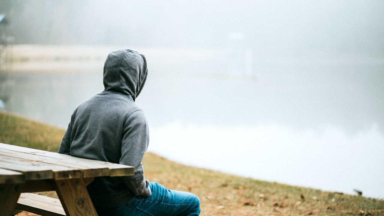 Person sitzt auf einer Holzbank bei einem nebligen Gewässer zu