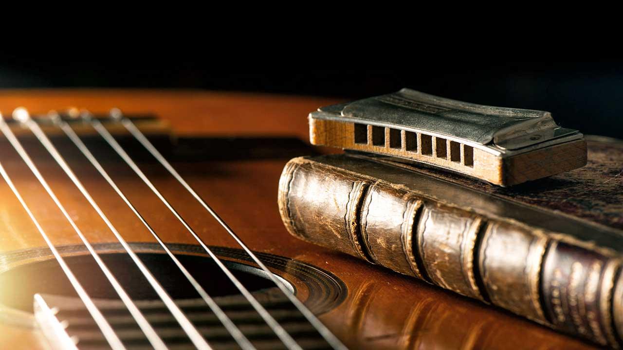 akustische Gitarre mit Mundharmonika und altem Buch