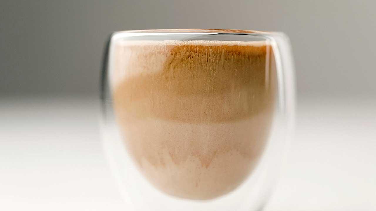 Glas, bis fast zum Rand gefüllt mit Kaffee