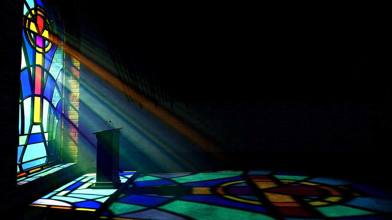 Licht fältt von einem Kirchenfenster auf eine Kanzel