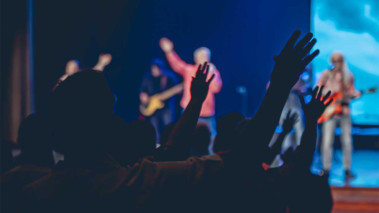 Blick von hinten auf die Bühne in einem dunkel beleuchteten Gottesdienst