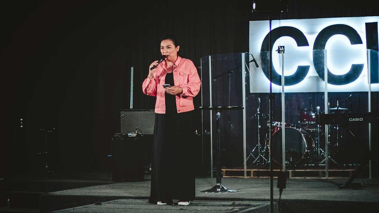 Frau auf einer Plattform spricht während eines Gottesdienstes