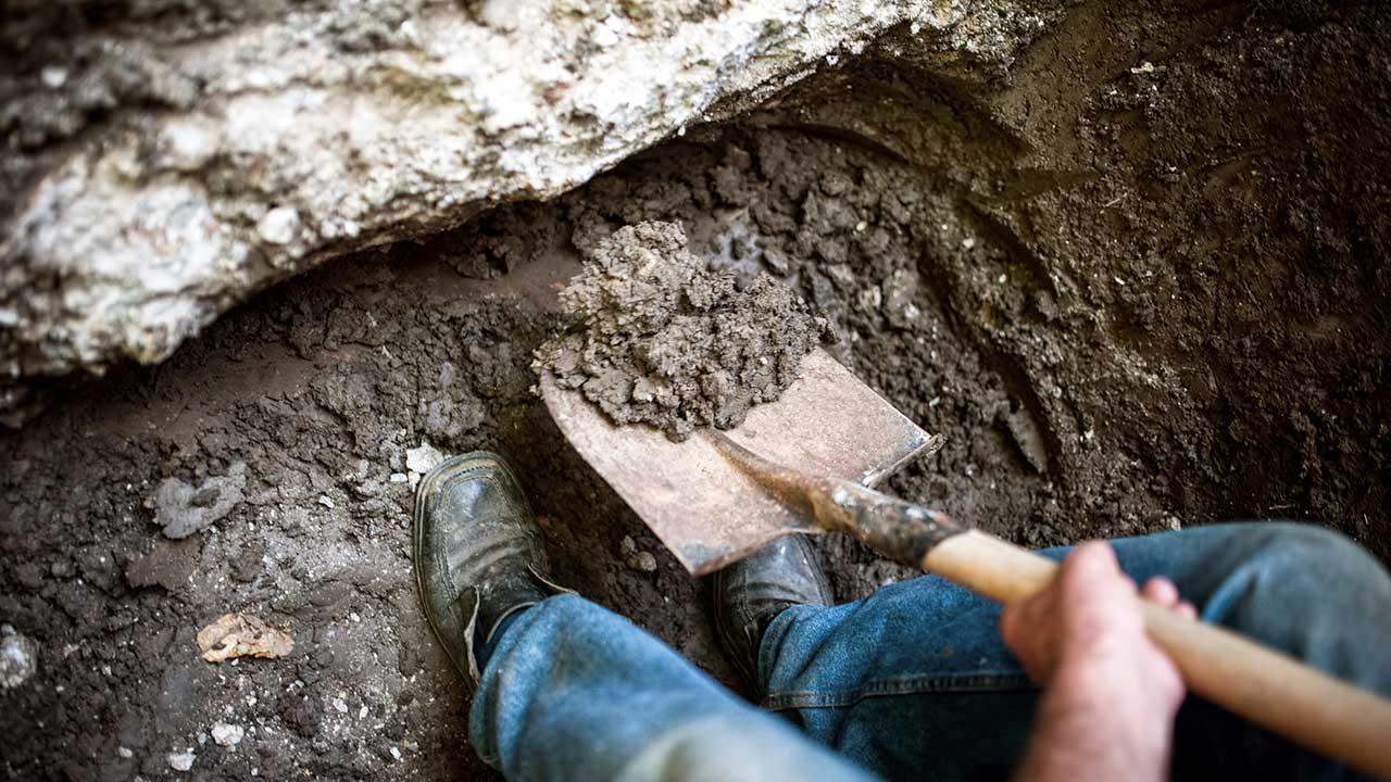 Jemand grabt mit einer Schaufel in einem Loch