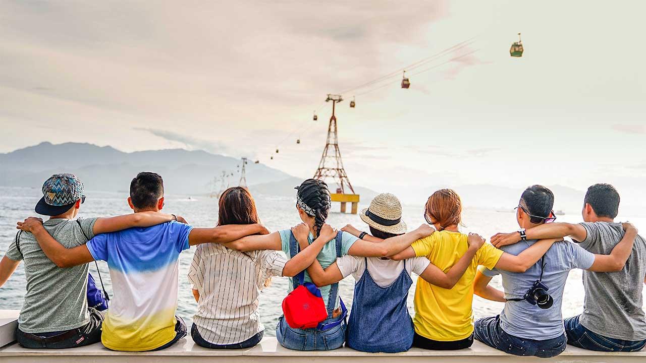 Rückansicht einer Gruppen von Teenagern, welche sitzen und sich über die Schulter umarmen