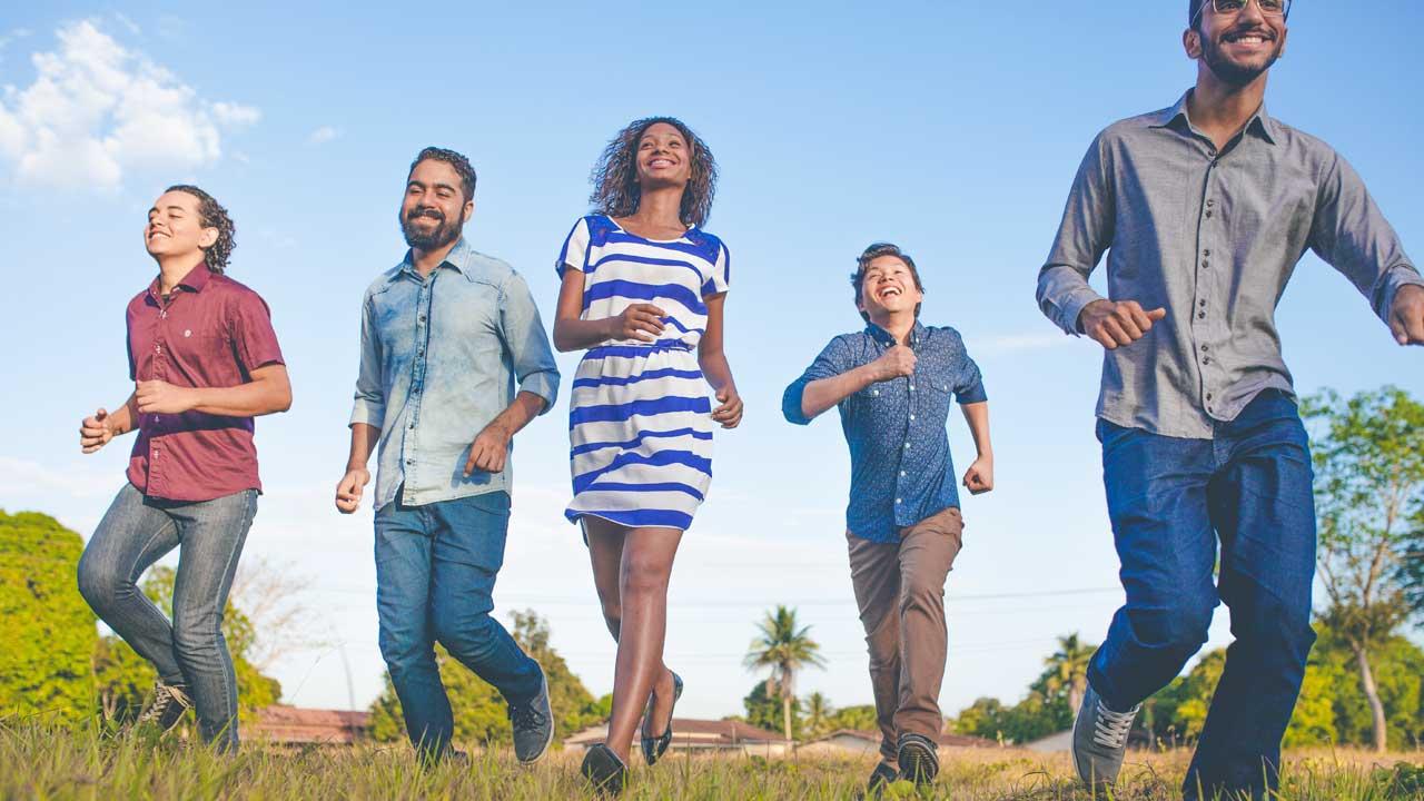 Eine Gruppe junger Erwachsener läuft vergnügt über eine Wiese