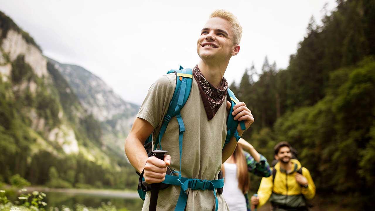 Gruppe junger Menschen wandert in einem Berggebiet mit See