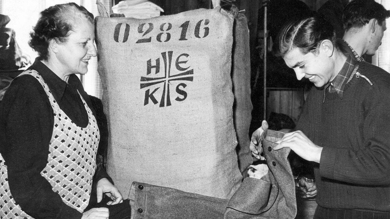 Zwei Frauen vor einem Jutesack, der mit «HEKS» beschriftet ist.