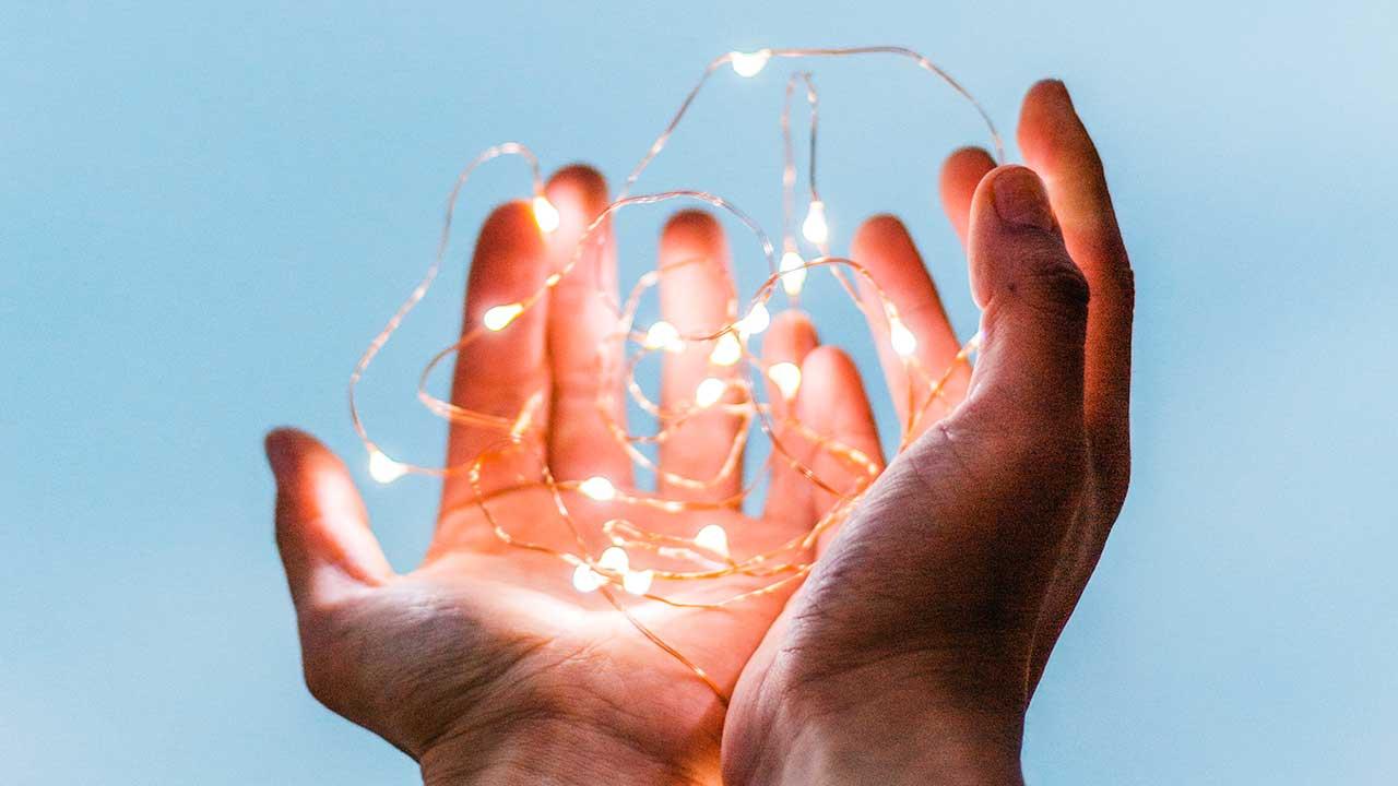 Zwei Hände halten Draht mit Glühbirnchen