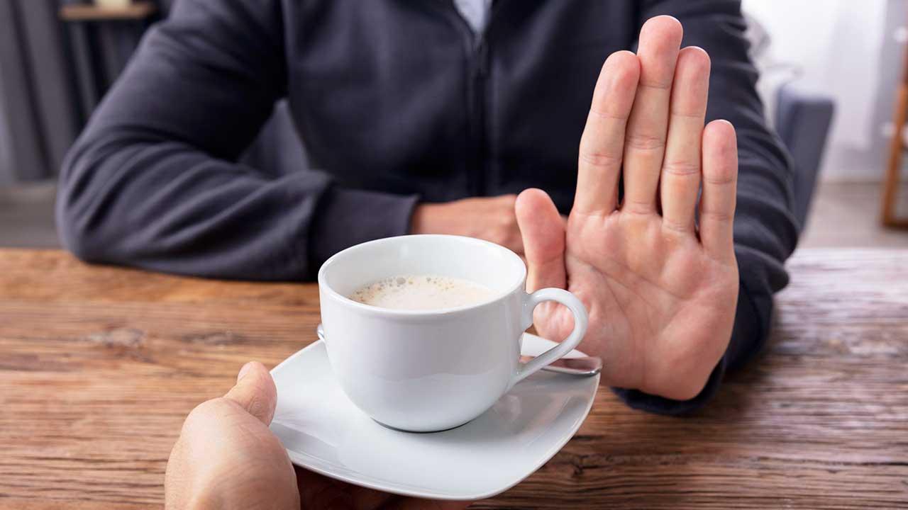 Männerhand lehnt einen Kaffee ab, der von einer anderen Hand gereicht wird