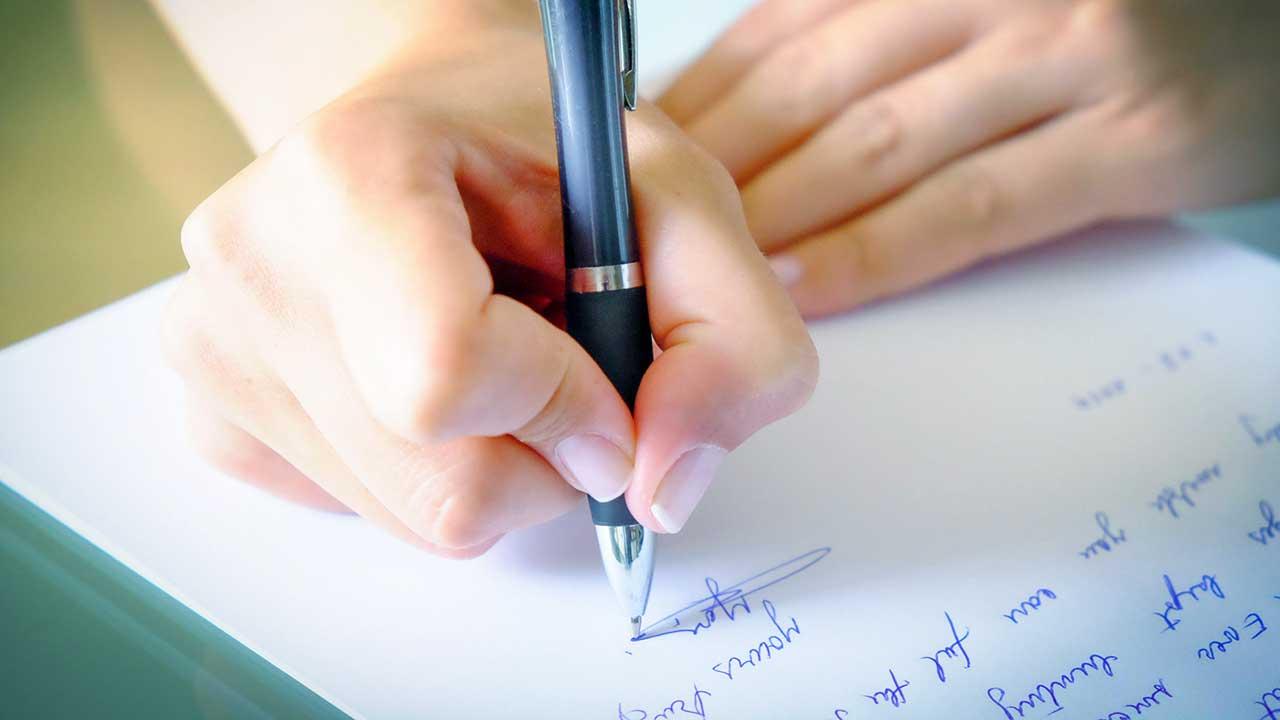 Hände mit Kugelschreiber auf beschriebenem Papier