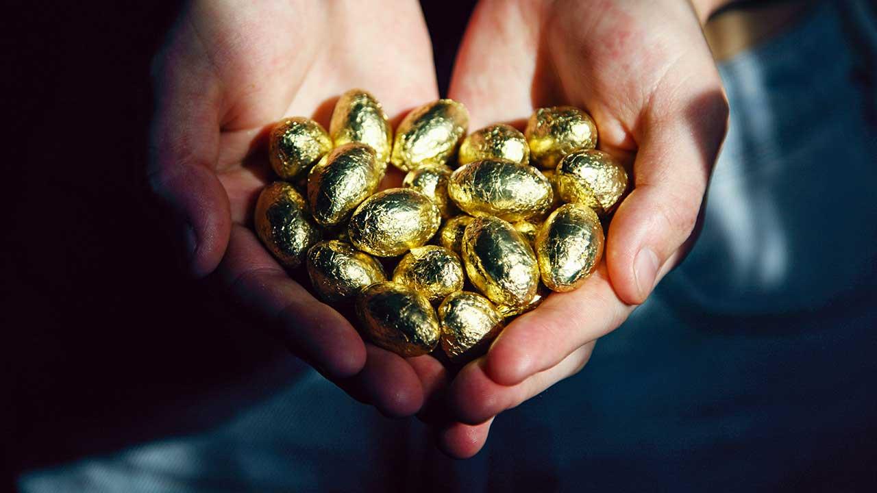 Zwei Hände offerieren Schokoladeneier, welche goldig verpackt sind