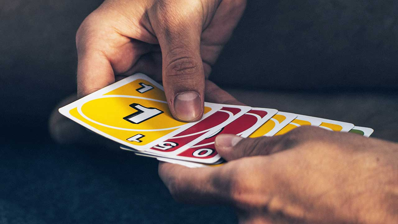 Hände halten Karten des Uno-Spiels