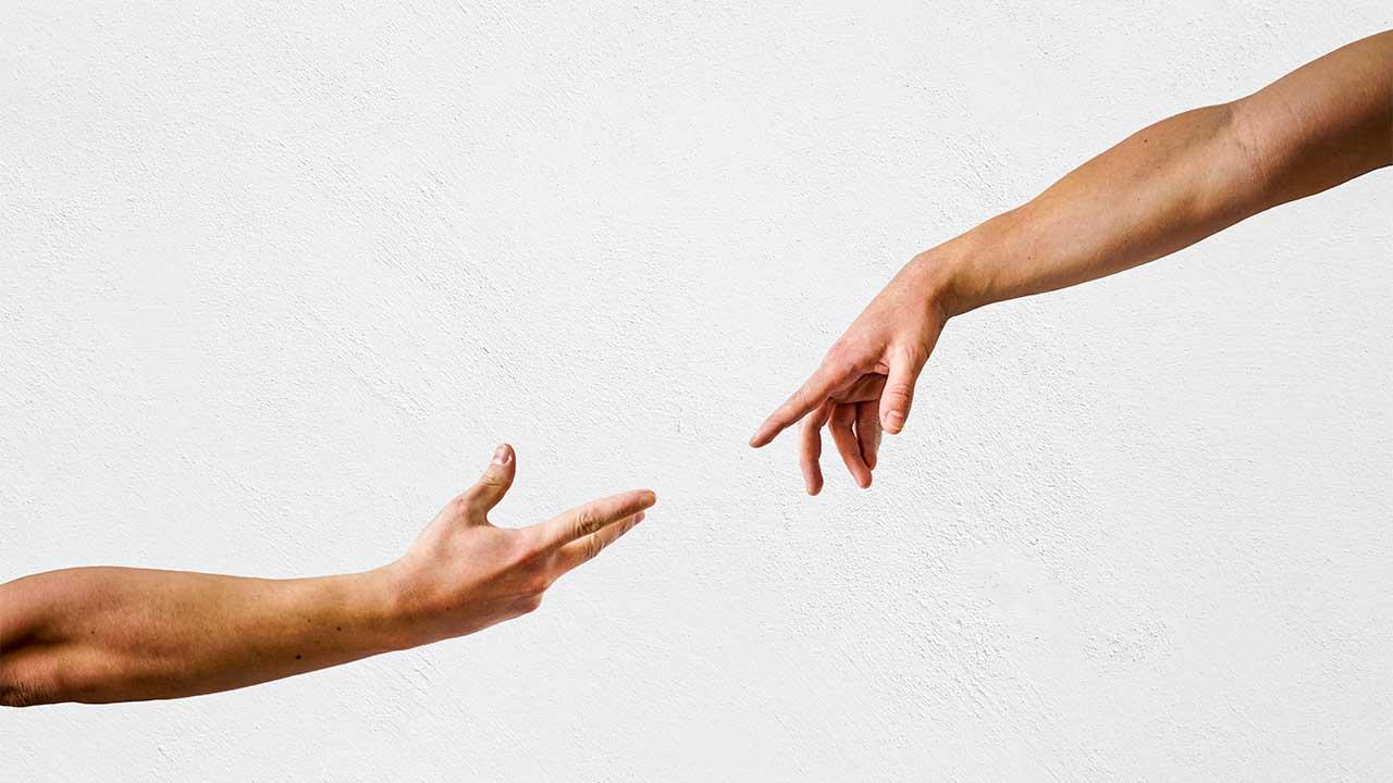 Zwei Hände strecken sich nacheinander aus