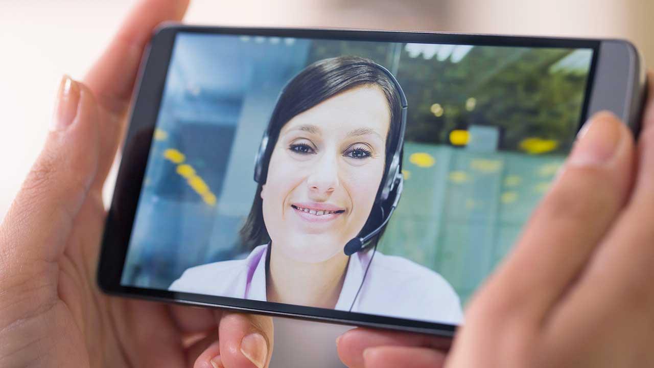 Hände halten ein Smartphone, auf welchem ein Videochat stattfindet