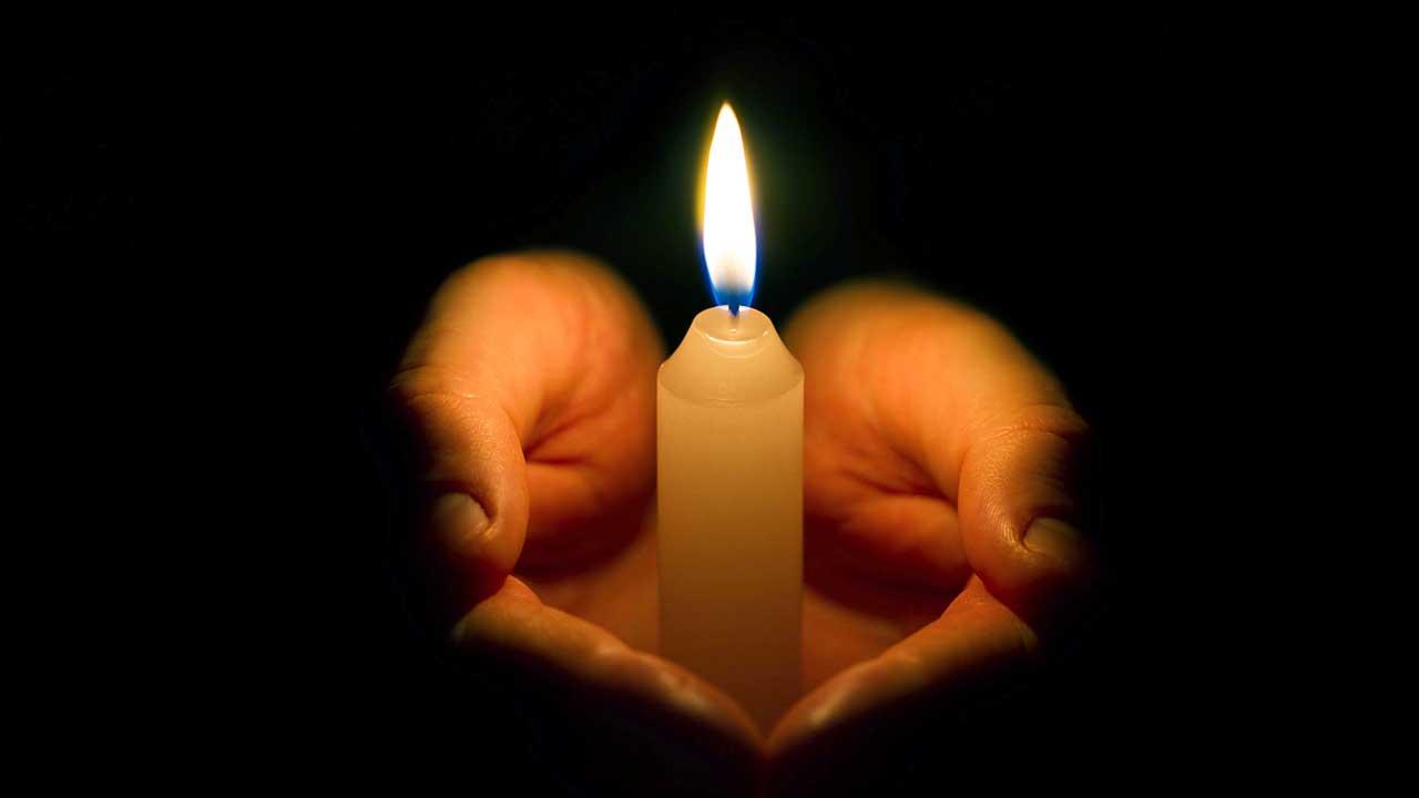 In der Dunkelheit halten Hände eine brennende Kerze