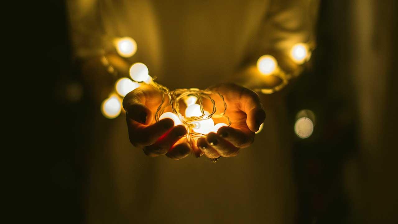 Betende Hände im Dunkeln mit Glühbirnchen drin