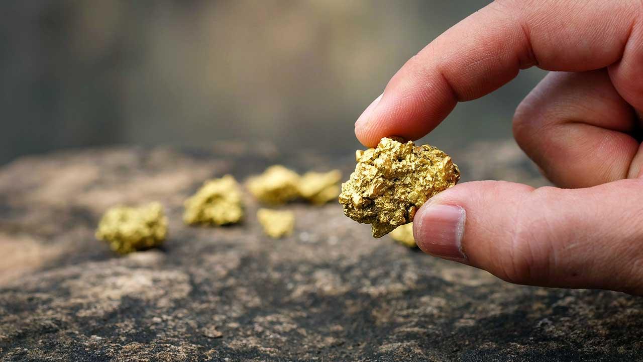 Finger halten ein Goldstück