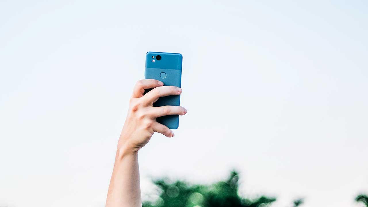 Hand hält ein Smartphone, um ein Selfie zu machen