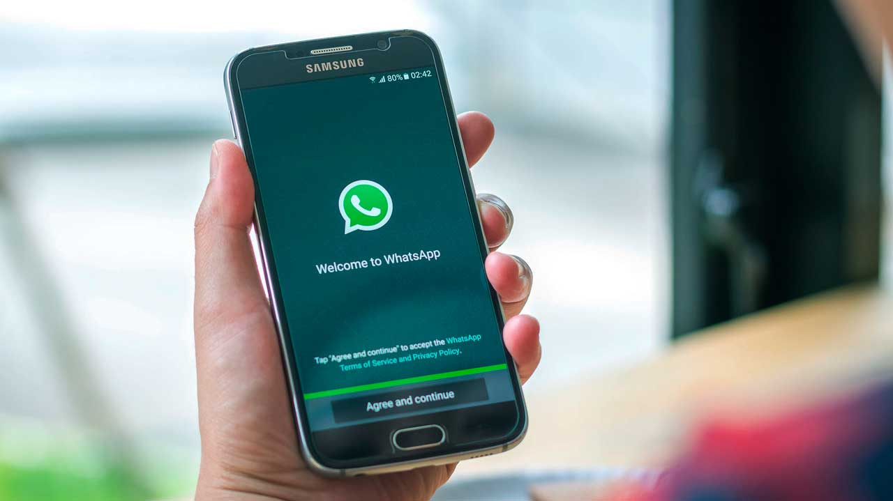 Hand hält Smartphone mit WhatsApp-Startbildschirm